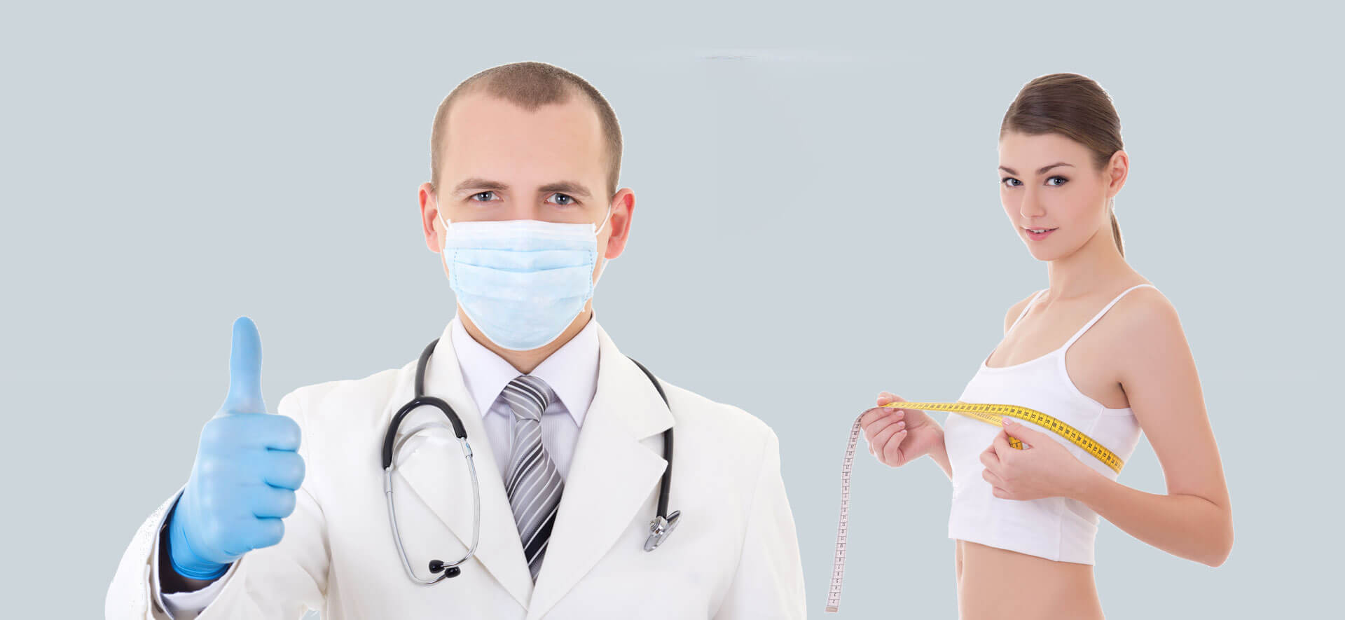 Doctor in mask and blue gloves giving thumbs up with female breast augmentation patient
