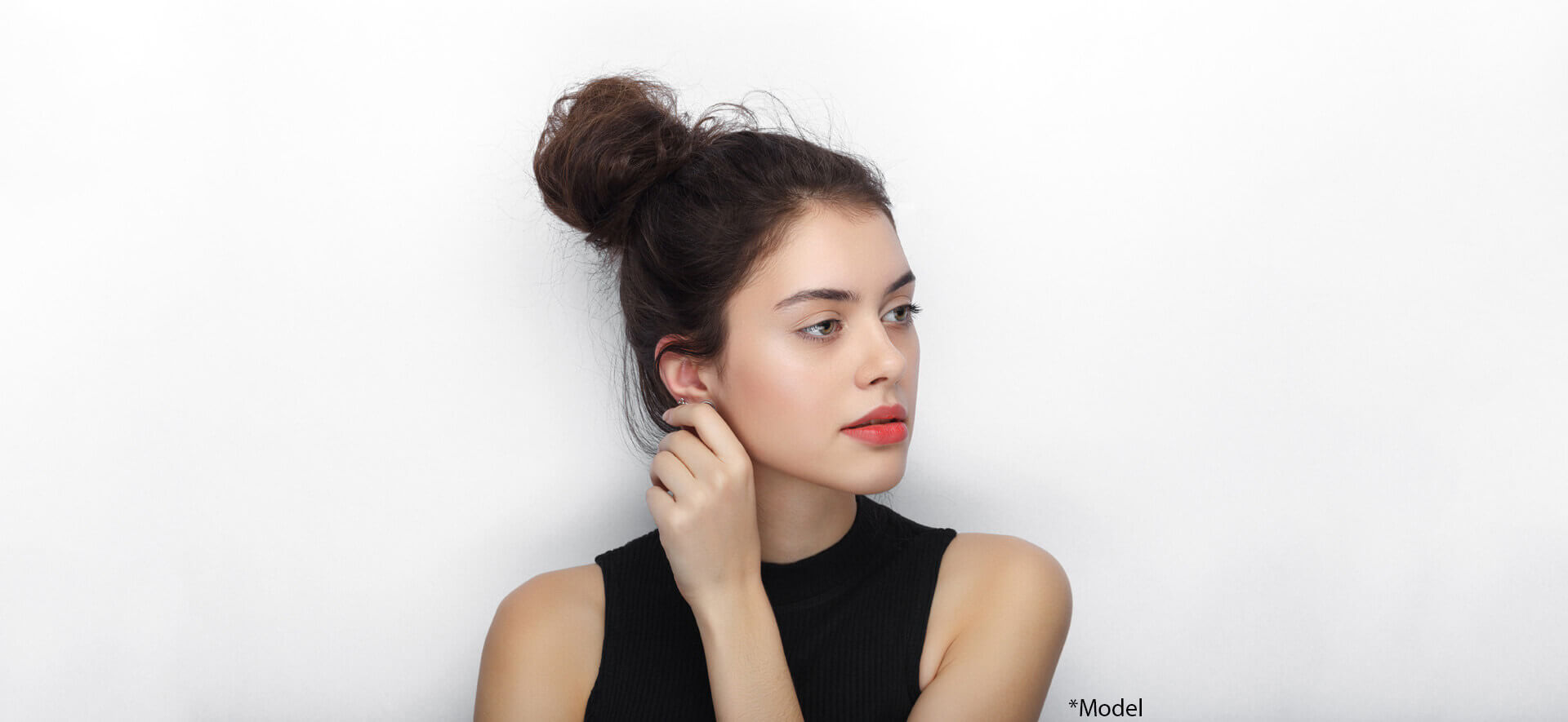 Beauty portrait of young adorable fresh looking brunette woman with high bun hairdo touching her ear