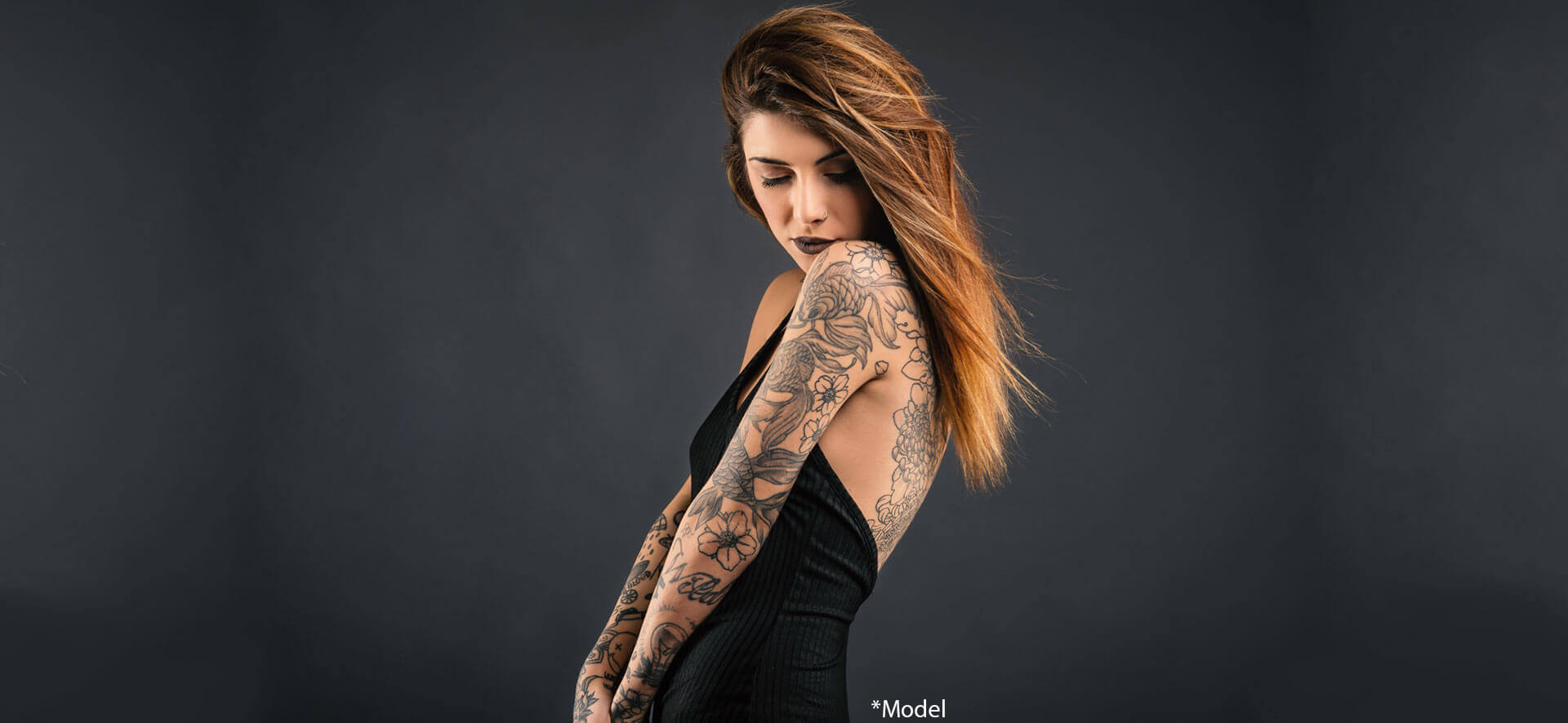 Intimate woman studio portrait with long black dress and tattoos against dark background