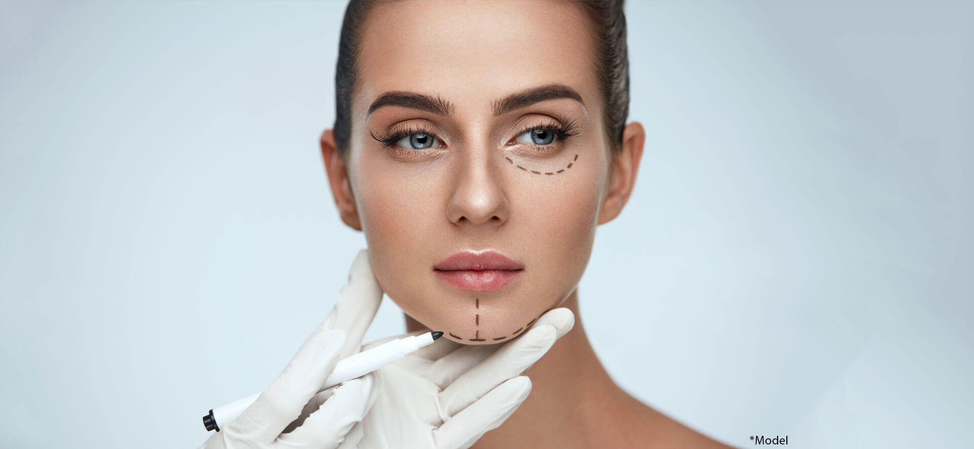 Beautician drawing surgical lines on woman face