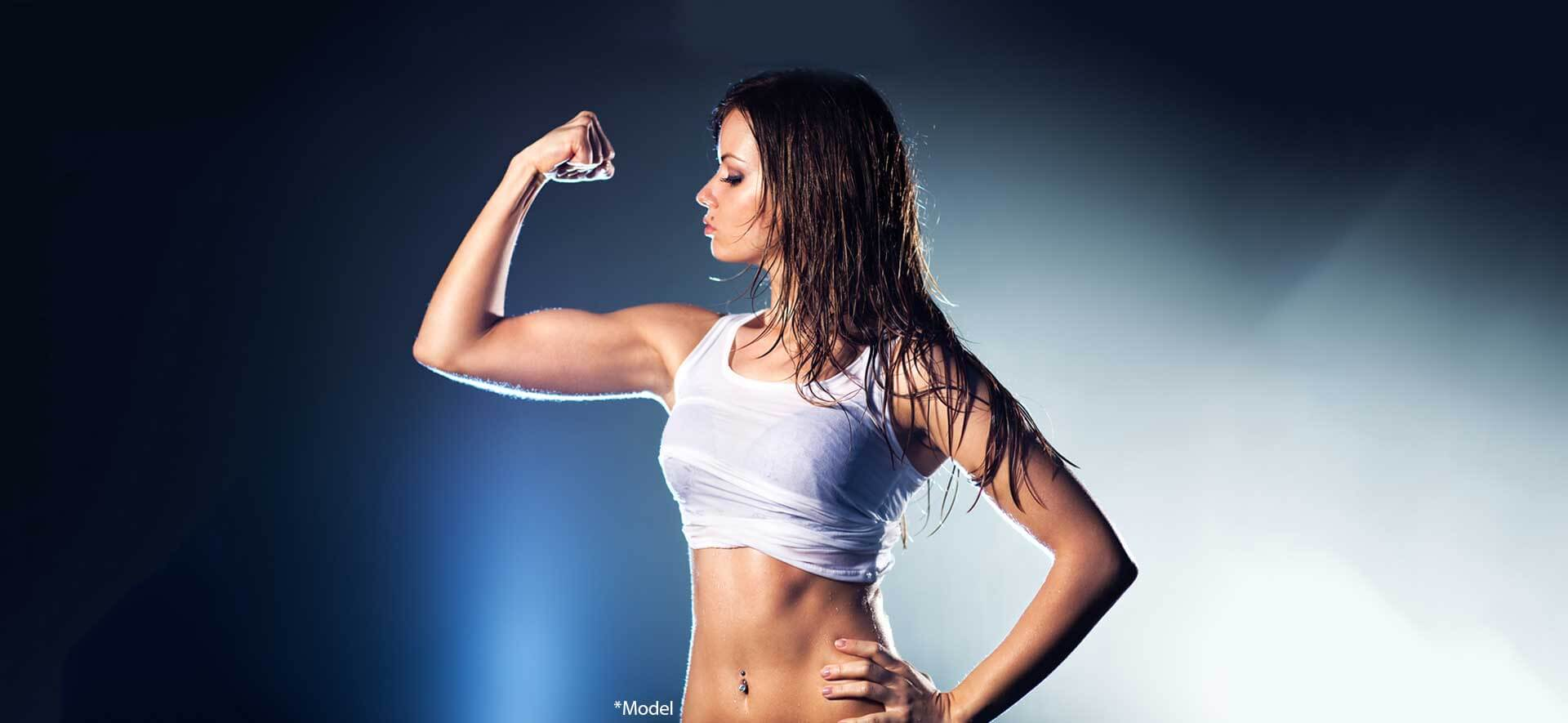 Young strong sexy woman showing her muscles