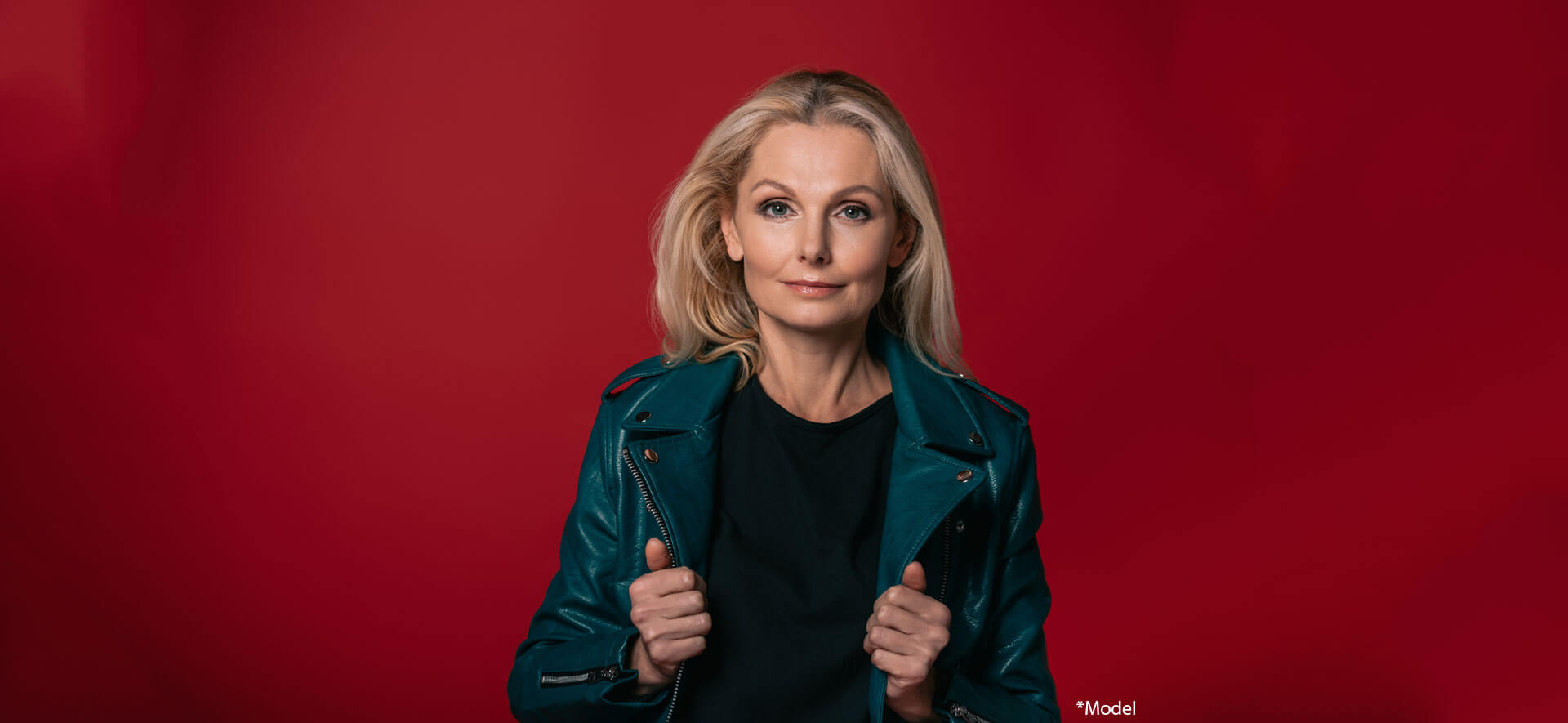 Stylish mature woman in leather jacket isolated on red
