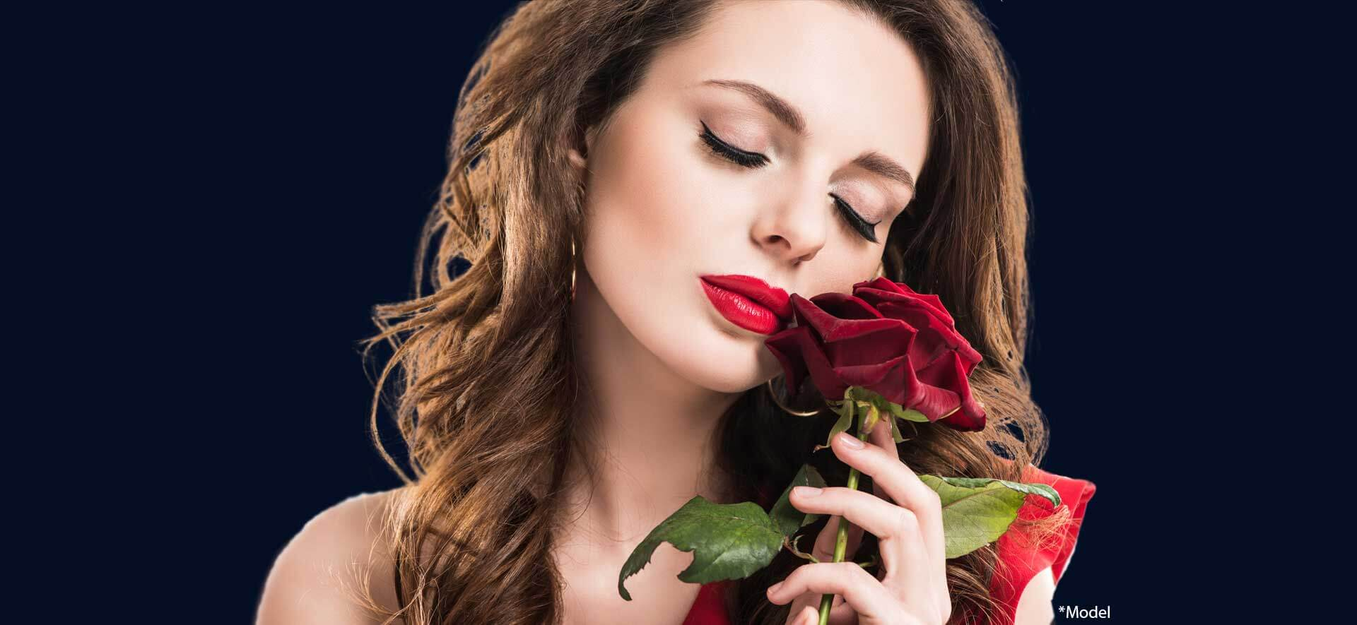 Stylish sensual girl touching face with rose isolated on dark background