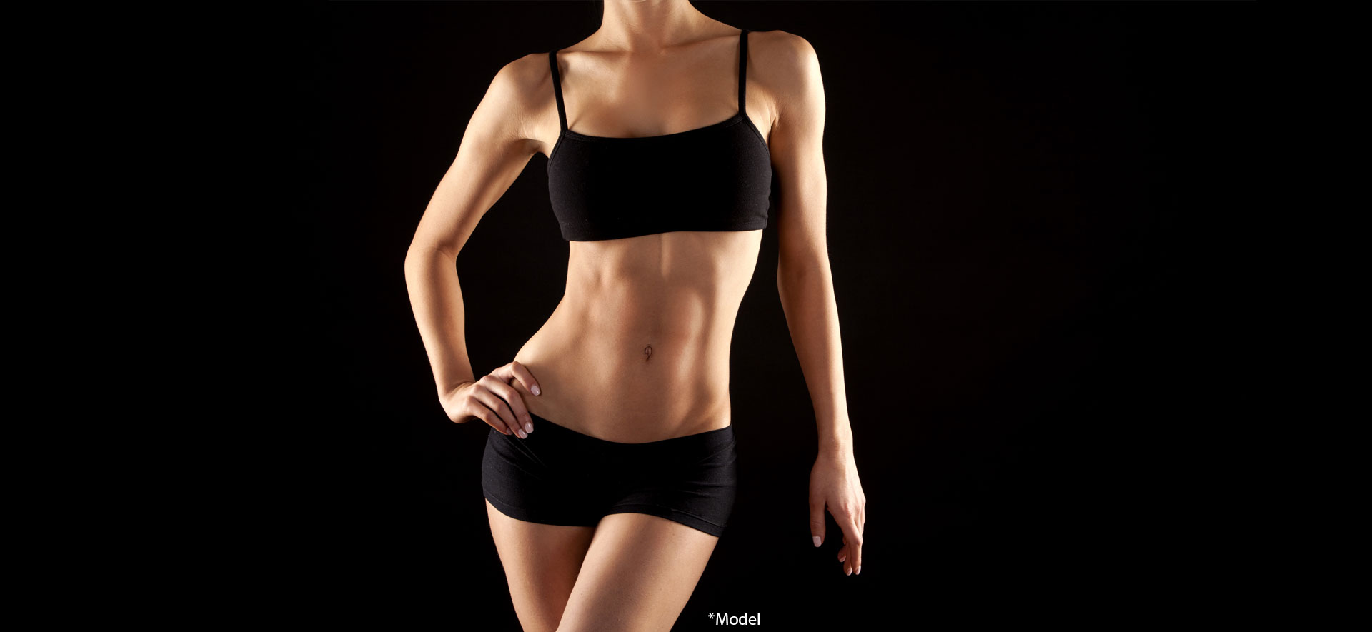 Female fitness model posing on black background